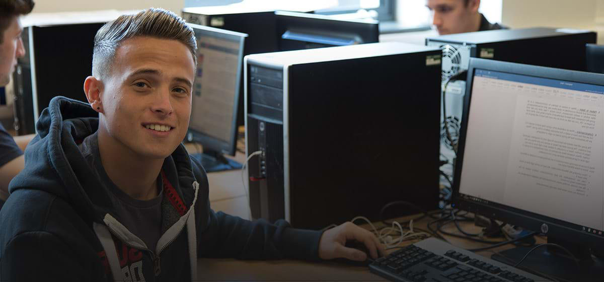 Photograph of a male student at his computer facing towards the camera smiling