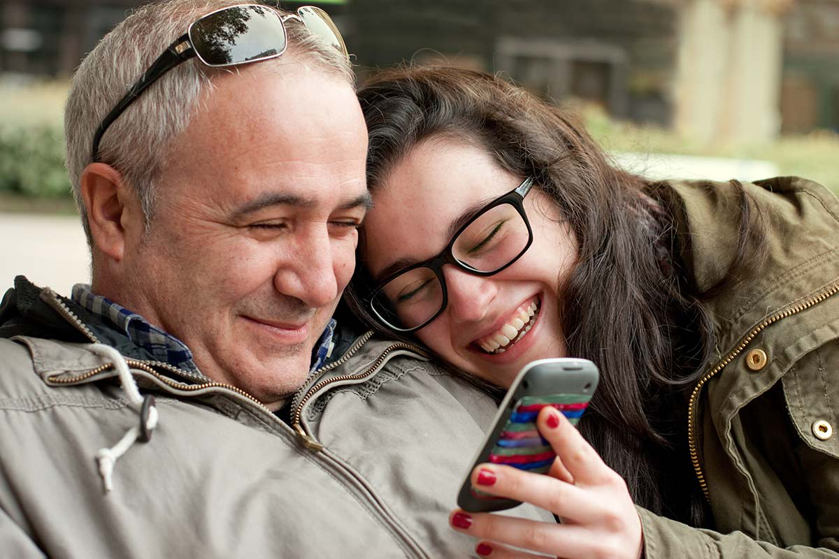 A father and daughter smiling using mobile phone.